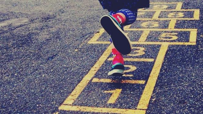 criança brincando na rua amarelinha